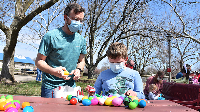 Boy wearing mask sitting at park picnic table looking through collection of eggs from an egg hunt.