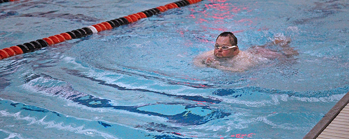 Participant with downs syndrome swimming breast stroke.